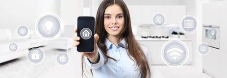 Mulher de sorriso home esperta que mostra a tela do telefone celular com símbolos imagem de stock