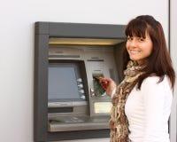 A mulher de sorriso introduz um cartão em um ATM Fotografia de Stock Royalty Free