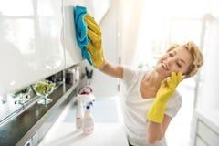 Mulher de sorriso loquaz que limpa o armário Imagem de Stock Royalty Free