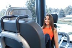 Mulher de sorriso magro que usa uma m?quina da imprensa do p? e colocando seus p?s na plataforma imagem de stock royalty free