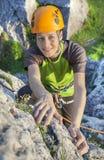 Mulher de sorriso, montanhista de rocha no capacete amarelo Foto de Stock