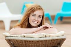 Mulher de sorriso na cadeira de plataforma Imagens de Stock