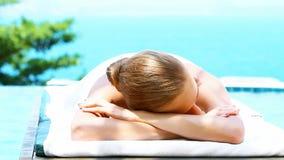 Mulher de sorriso na cama dos termas ao lado da piscina