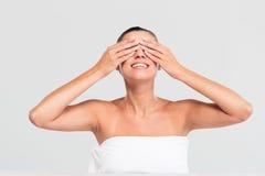 A mulher de sorriso na coberta de toalha eyes com mãos Imagens de Stock
