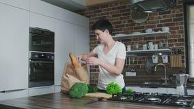 Mulher de sorriso na cozinha com um saco da compra de mantimentos filme