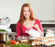 Mulher de sorriso na massa de fatura vermelha ou omlet na cozinha Foto de Stock Royalty Free
