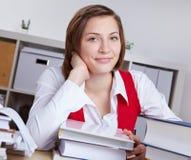Mulher de sorriso na mesa com livros Foto de Stock Royalty Free