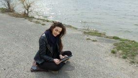 A mulher de sorriso na praia que usa sua tabuleta mostra vídeos de arquivo