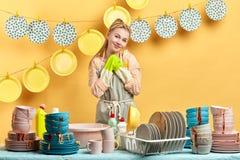 Mulher de sorriso nas luvas e posição do avental atrás da tabela com pratos sujos imagens de stock royalty free