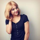 Mulher de sorriso natural bonito com o penteado louro curto que olha o ha Fotografia de Stock