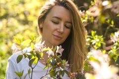 Mulher de sorriso no arbusto de florescência no dia de verão ensolarado foto de stock