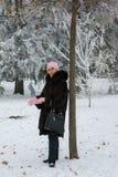 A mulher de sorriso no casaco de pele está ficando perto da árvore no parque fotografia de stock