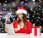 Mulher de sorriso no chapéu de Santa com o PC do presente e da tabuleta Imagem de Stock Royalty Free