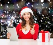 Mulher de sorriso no chapéu de Santa com o PC do presente e da tabuleta Imagens de Stock Royalty Free