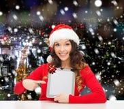 Mulher de sorriso no chapéu de Santa com o PC do presente e da tabuleta Foto de Stock