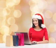 Mulher de sorriso no chapéu de Santa com sacos e portátil Fotografia de Stock Royalty Free