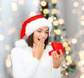 Mulher de sorriso no chapéu do ajudante de Santa com caixa de presente Fotos de Stock