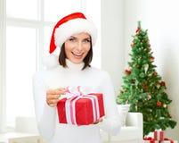 Mulher de sorriso no chapéu do ajudante de Santa com caixa de presente Imagem de Stock Royalty Free
