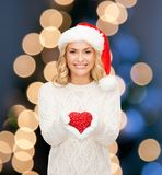 Mulher de sorriso no chapéu do ajudante de Santa com coração vermelho Fotos de Stock