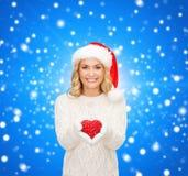 Mulher de sorriso no chapéu do ajudante de Santa com coração vermelho Fotos de Stock Royalty Free