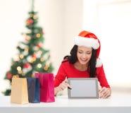 Mulher de sorriso no chapéu do ajudante de Santa com PC da tabuleta Foto de Stock Royalty Free