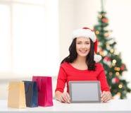 Mulher de sorriso no chapéu do ajudante de Santa com PC da tabuleta Fotografia de Stock Royalty Free