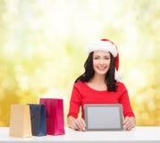 Mulher de sorriso no chapéu do ajudante de Santa com PC da tabuleta Imagens de Stock Royalty Free