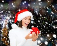 Mulher de sorriso no chapéu do ajudante de Santa com caixa de presente Fotos de Stock Royalty Free