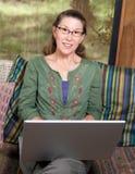 Mulher de sorriso no computador portátil foto de stock