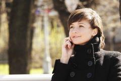 Mulher de sorriso no parque com telemóvel Fotografia de Stock