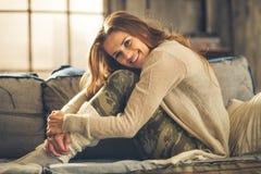 Mulher de sorriso no sofá no sótão, abraçando seus joelhos imagem de stock