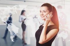 Mulher de sorriso no telefone no escrit?rio, rede do mundo fotografia de stock