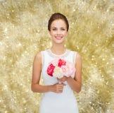 Mulher de sorriso no vestido branco com o ramalhete das rosas Foto de Stock