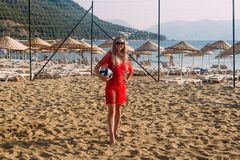 Mulher de sorriso no vestido da praia com posição na areia, férias da bola imagens de stock royalty free