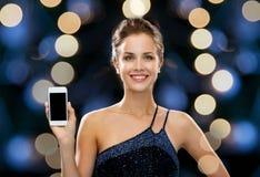 Mulher de sorriso no vestido de noite com smartphone Fotos de Stock