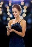 Mulher de sorriso no vestido de noite com smartphone Fotografia de Stock