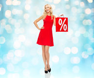 Mulher de sorriso no vestido vermelho com saco de compras Foto de Stock