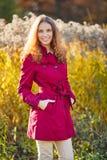 Mulher de sorriso nova bonita em uma capa de chuva vermelha Fotos de Stock Royalty Free