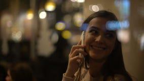 Mulher de sorriso nova bonita que conversa no telefone e no amigo de espera no café acolhedor vídeos de arquivo