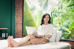 Mulher de sorriso nova bonita que trabalha no portátil ao sentar-se sobre Fotografia de Stock