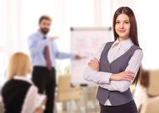 A mulher de sorriso nova com braço dobrou-se no escritório Fotos de Stock Royalty Free