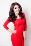 Mulher de sorriso nova com o vestido vermelho do cabelo marrom encaracolado longo Fotos de Stock