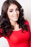 Mulher de sorriso nova com o vestido vermelho do cabelo marrom encaracolado longo fotografia de stock
