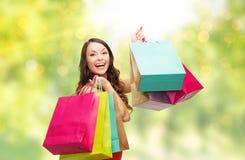 Mulher de sorriso nova com os sacos de compras sobre luzes fotos de stock