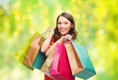 Mulher de sorriso nova com os sacos de compras sobre luzes fotografia de stock royalty free
