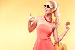 A mulher de sorriso nova com sacos de compras faz seu polegar acima, isolado no fundo amarelo que guarda o cartão da venda imagens de stock