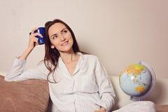 A mulher de sorriso nova com uma xícara de café ou um chá azul, sentando-se no sofá na sala e quer descansar, marido, casa nova,  fotos de stock royalty free