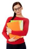 Mulher de sorriso nova do estudante que guarda livros fotografia de stock royalty free