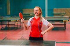 A mulher de sorriso nova está atrás do tênis de mesa dentro foto de stock royalty free