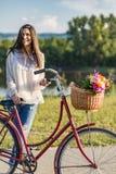 A mulher de sorriso nova monta uma bicicleta Fotografia de Stock Royalty Free